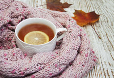 Cup of hot tea with lemon and scarf Stock Images
