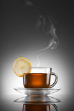 Cup of hot tea with lemon and steam Stock Photos
