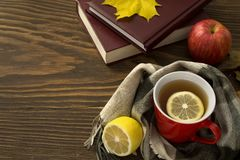 A cup of hot tea with a lemon wrapped in a scarf on a wooden table. With yellowed leaves in a rustic style Stock Photography