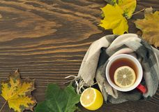 A cup of hot tea with a lemon wrapped in a scarf on a wooden table. With yellowed leaves in a rustic style Stock Photo