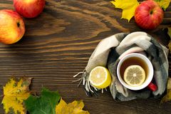 A cup of hot tea with a lemon wrapped in a scarf on a wooden table. With yellowed leaves in a rustic style Stock Images