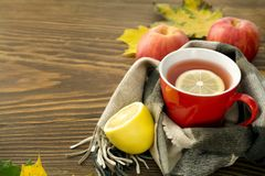 A cup of hot tea with a lemon wrapped in a scarf on a wooden table. With yellowed leaves in a rustic style Royalty Free Stock Photo