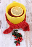 Cup of hot tea with lemon wrapped woolen scarf and cotoneaster, warming beverage for flu Stock Image