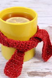 Cup of hot tea with lemon wrapped woolen scarf, warming beverage for flu and cold Royalty Free Stock Image