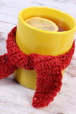 Cup of hot tea with lemon wrapped woolen scarf, warming beverage for flu and cold Royalty Free Stock Photography