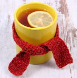 Cup of hot tea with lemon wrapped woolen scarf, warming beverage for flu and cold Stock Image