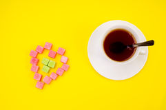 Cup of hot tea and lumps sugar. Isolated on yellow Royalty Free Stock Photos