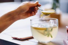 A cup of hot tea with mint and lemon mixes the girl with a spoon. In cafe Stock Photography