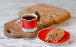 Cup of hot tea and piece of honey cake on red saucer. Rustic style. Royalty Free Stock Photo