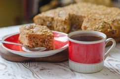 Cup of hot tea and piece of honey cake on red saucer. Rustic style. Royalty Free Stock Image