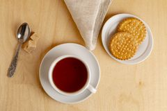 Cup of hot tea on a saucer, fresh biscuits, brown sugar and a cloth napkin. royalty free stock images
