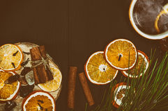 Cup of hot tea with slices of lemon and orange on a black wooden Royalty Free Stock Photography
