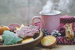A cup of hot tea stands on a wooden table next to a wooden plate on which are gingerbread cookies made from orange stock images