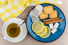 Cup of hot tea, sugar, cinnamon sticks, slices of lemon Stock Photo