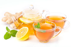 Cup of hot tea and a teapot. ginger, lemon and mint Royalty Free Stock Photos