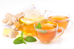 Cup of hot tea and a teapot. ginger, lemon and mint Stock Photos