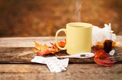 Cup with hot tea and thermometer showing high temperature along Stock Photography