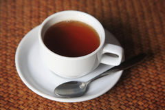 Cup of hot tea on weave table Royalty Free Stock Photo