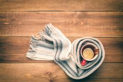 A cup of hot tea is wrapped in a scarf. Stock Photo