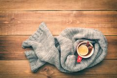 A cup of hot tea is wrapped in a scarf. Stock Photography