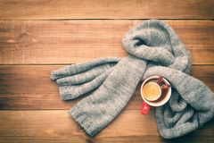 A cup of hot tea is wrapped in a scarf. Stock Photos
