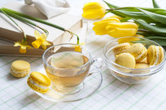 A cup of hot tea, yellow tulips, yellow daffodils, old books and lemon macaroons on a light background Stock Photography