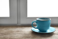 Cup of hot winter drink on wooden sill near window, space for text. Cozy season stock photos