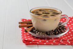 A Cup of iced coffee and cinnamon on a red cloth on a white wooden table royalty free stock photos