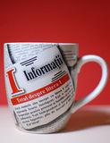 A Cup of Informations. A cup with newspaper theme on a red background Royalty Free Stock Photography