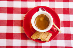 A cup of the italian espresso. A cup of the typical italian coffee espresso in a red cup with a red saucer on a red and white checkered tablecloth Stock Photo
