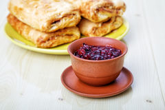 Cup with jam and sweet rolls Stock Photos