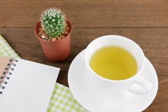 The cup of Japanese green tea and little cactus in plant pot and small note book with green cotton fabric Royalty Free Stock Photography
