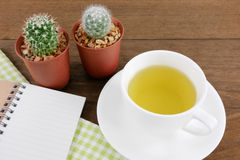 The cup of Japanese green tea and little cactus in plant pot and small note book with green cotton fabric Royalty Free Stock Images