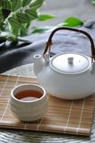 A Cup of Japanese Hot Tea. Acup of Japanese hot tea wh tea pot on bamboo mat royalty free stock photography