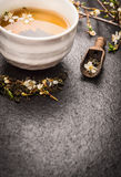 Cup of Jasmine tea with fresh flowers on dark background. Copy space stock images