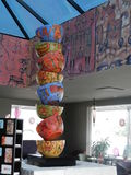 Cup of Joe?. Eight artfully colored large cups in a vertical sculpture at a coffee cafe in Lake Chapala, Mexico, with surrounding artwork on the walls.  The Stock Photo