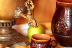 Cup, jug and samovar. Samovar, a cup and a jug on the wooden table Stock Images