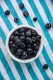 A Cup Of Juicy Blueberries At A Bright Blue Stripy Background. A white cup with juicy blueberries at the stripy blue-and-white background stock photography