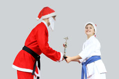 Cup karate Santa Claus with a black belt gives little sportsman stock photo