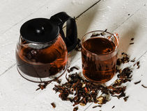 Cup of Karkadeh Red Tea with Dry Flowers and kettle on a wooden Stock Images