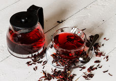 Cup of Karkadeh Red Tea with Dry Flowers and kettle on a wooden Stock Photo