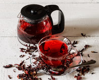 Cup of Karkadeh Red Tea with Dry Flowers and kettle on a wooden Stock Image