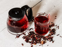 Cup of Karkadeh Red Tea with Dry Flowers and kettle on a wooden Royalty Free Stock Photo