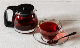 Cup of Karkadeh Red Tea and kettle on wooden table Royalty Free Stock Image