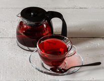 Cup of Karkadeh Red Tea and kettle on wooden table Royalty Free Stock Photo