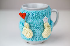 Cup in knitted sweater with hands and red heart. Stock Photos