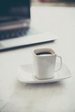 Cup and laptop Stock Photos