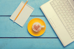 Cup and laptop with note Stock Photography
