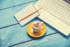 Cup and laptop with note Stock Photo