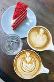 Cup of latte art coffee and cake. On wood table royalty free stock photography